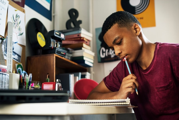 Teenage boy in a bedroom doing work thinking