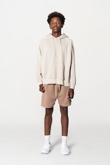 Teenage boy in beige hoodie apparel studio portrait