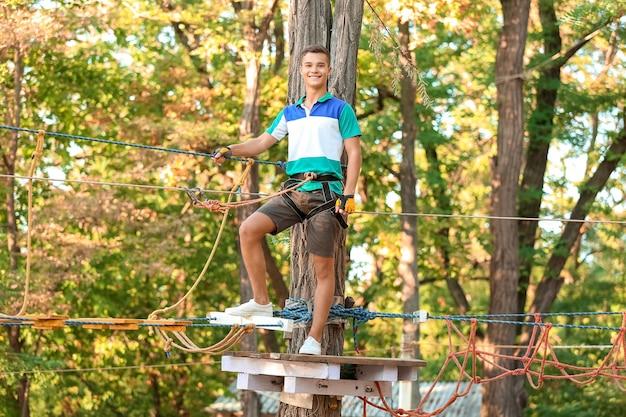 アドベンチャーパークに登る10代の少年