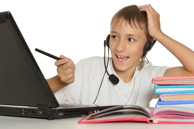 Подросток делает домашнее задание с ноутбуком на белом фоне