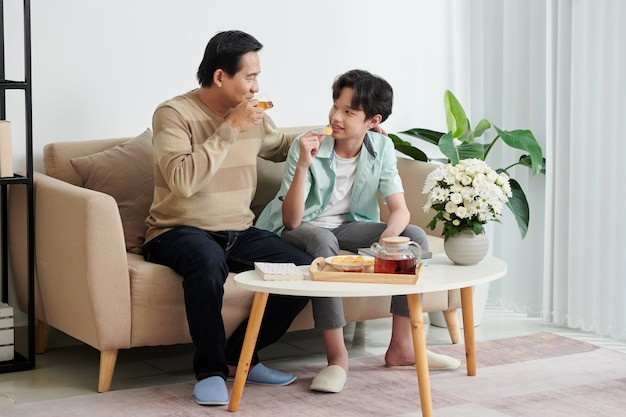 Teenage boy eating potato chips and discussing news with dad who is drinking tea