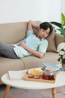 Teenage boy fell asleep after reading book lying on sofa at home