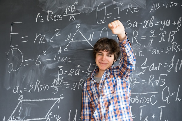 Teenage boy finding idea with complicated math formulas on black board
