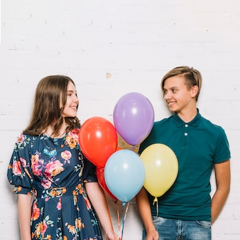 Teenage boy and girl holding balloons in hand looking at each other