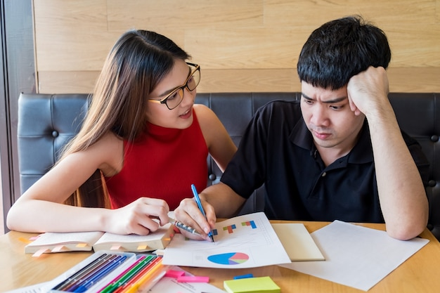Teenage boy and girl students, doing homework together on a notebook