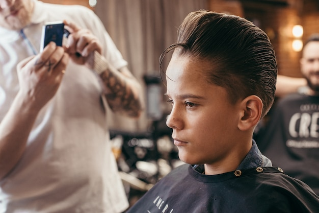Teenage boy haircuts hairdresser in the barber shop. fashionable stylish retro hairstyle