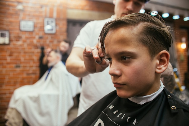 Teenage boy haircuts hairdresser in barber shop