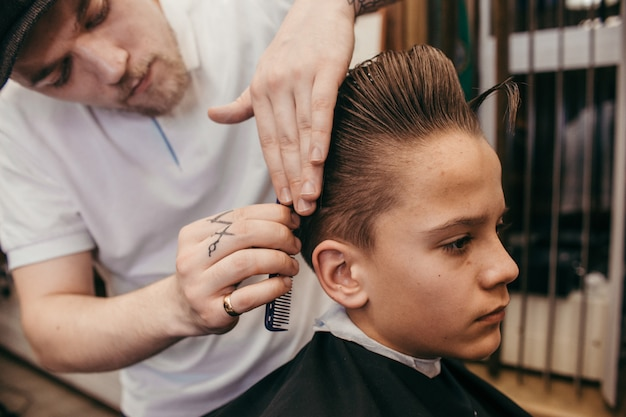 Teenage boy haircuts hairdresser in the barber shop