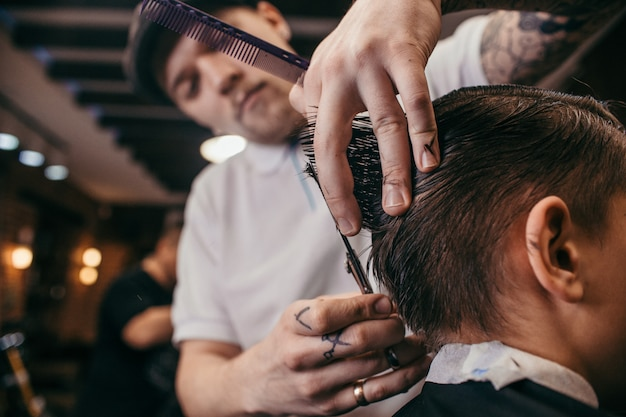 Teenage boy haircuts hairdresser in barber shop