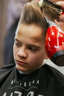 10대 소년이 이발소에서 미용사를 이발합니다. 세련된 세련된 복고풍 헤어스타일. 아름다운 머리를 한 아이의 초상화. 러시아, 스베르들로프스크, 2019년 2월 12일