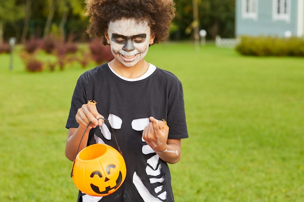 Teenage boy on halloween holding candy bag