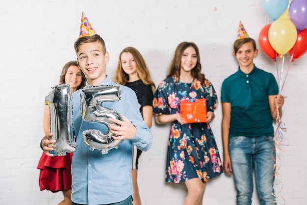 A teenage boy holding grey number 15 foil balloon number standing in front of friends