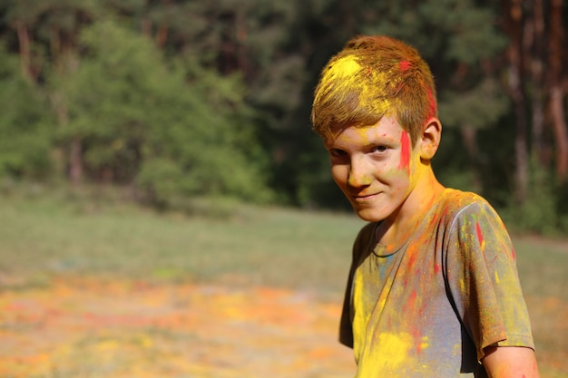 Teenage boy in holi paints. portrait of a boy at the holi festival of colors