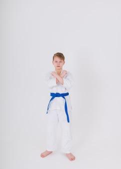 파란색 벨트가 달린 흰색 기모노를 입은 십대 소년은 흰 벽에 포즈를 취합니다.