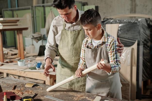 Подросток в фартуке гладит доску наждачной бумагой под контролем отца в столярной мастерской