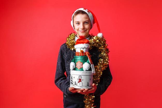 Подросток в новогодней шапке и мишуре на шее держит рождественскую подарочную коробку на красной стене