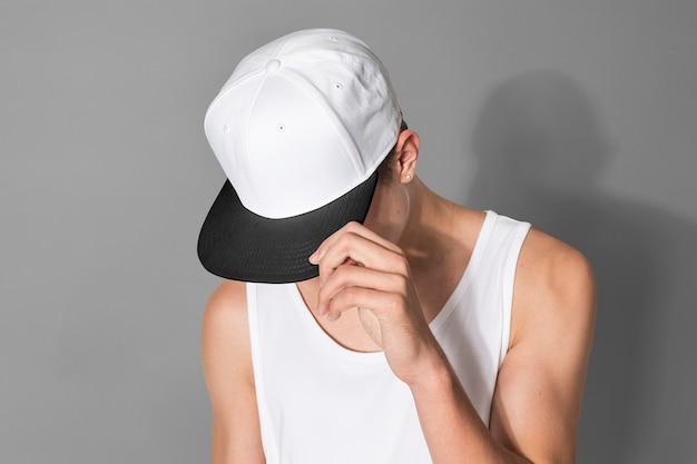 흰색 snapback 모자와 탱크 탑 스트리트 패션 촬영에서 10 대 소년