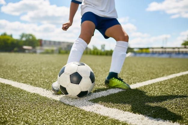 10代の少年がサッカーのフィールドでボールを蹴る