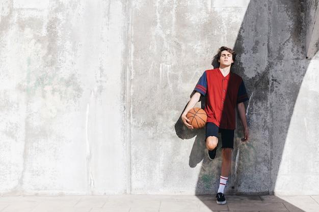 バスケットボール、壁に傾いている十代の少年