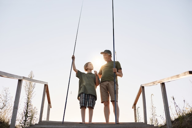Teenage boy learning to fish with fishing rod, grandpa teaching his grandson to catch fishes, full length portrait on wooden pontoon with stairs, beautiful sunset.