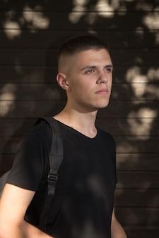 Teenage boy looking at camera on background of urban wall