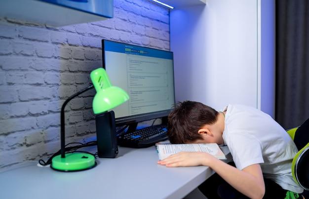 Подросток лежал на рабочем столе. сон во время учебы и подготовки к домашнему заданию. компьютерное электронное обучение. концепция измученного и утомленного студента.