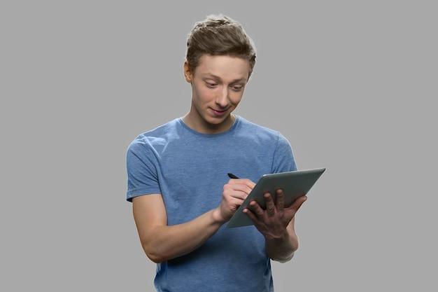 디지털 태블릿에 메모를 만드는 십 대 소년. 회색 배경에 태블릿 pc에서 작업하는 잘 생긴 십 대 남자.