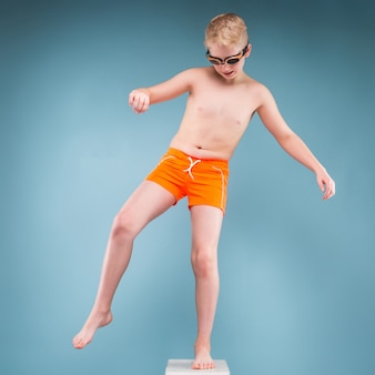 Teenage boy in orange shorts and swimming glasses stand on one leg