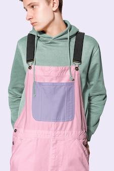 Teenage boy in pink dungarees and green hoodie streetwear photoshoot