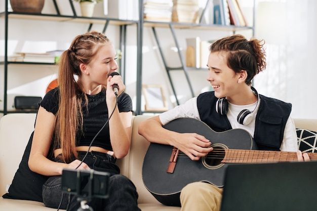 Teenage boy playing guitar when his sister singing song in microphone when recording video on smartphone
