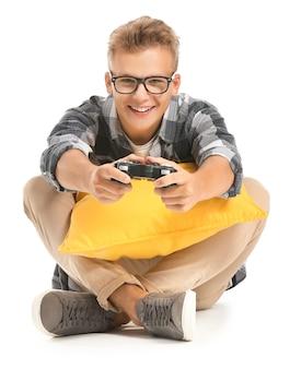 白い背景でビデオゲームをプレイする10代の少年