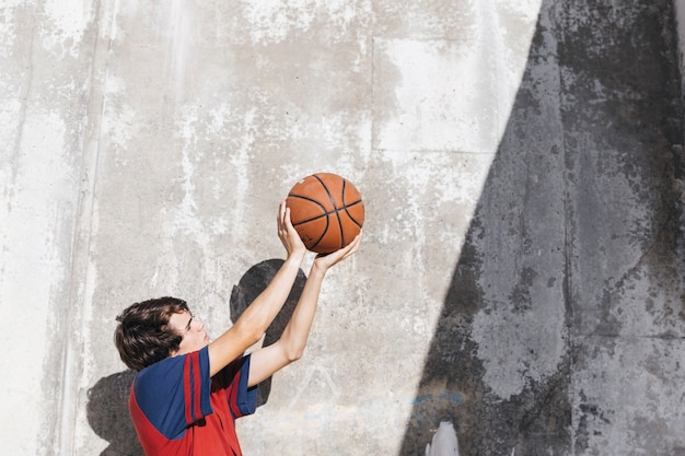 Teenage boy practicing basketball in front of wall