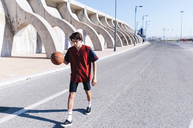 Teenage boy practicing basketball on road