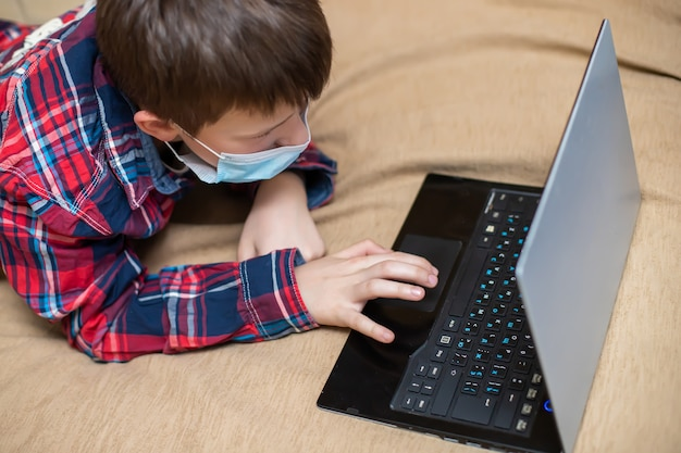 Teenage boy in protective medical mask coughs in fist. child remotely does lessons lying on bed near laptop. concept of learning and playing children on computer.