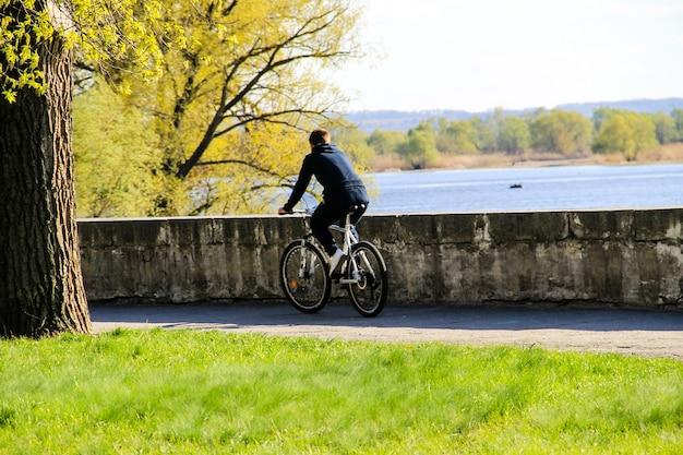 Подросток, езда на велосипеде в городском парке