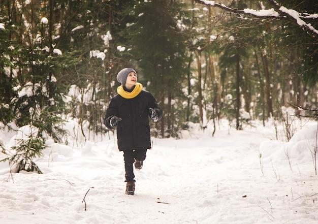A teenage boy runs through the winter forest.