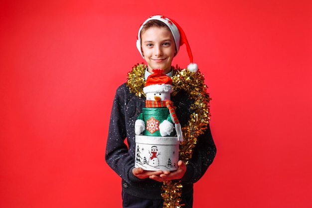 Teenage boy in santa hat and tinsel on neck holding christmas gift box on red wall