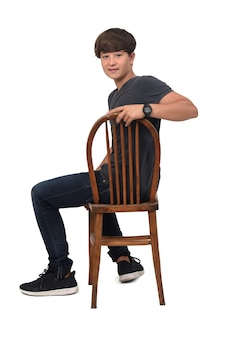 Teenage boy sitting on a chair, looking at camera