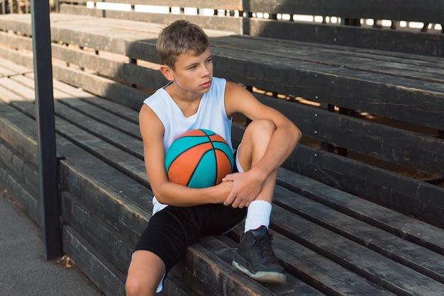 ボールバスケットボール選手ティーンエイジャーを保持しているベンチに座っている10代の少年