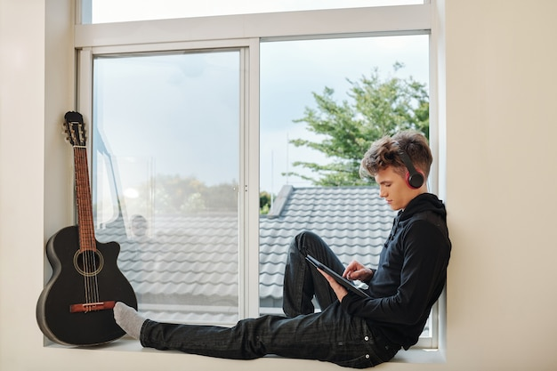 Мальчик-подросток сидит на подоконнике с наушниками и смотрит веб-семинар или фильм на планшетном компьютере