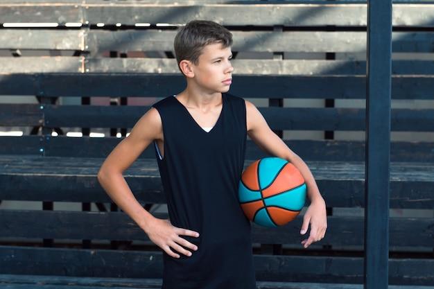 スポーツグラウンドのバスケットボール選手のティーンエイジャーで一人で立っている10代の少年