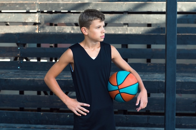 Teenage boy standing alone at sports ground basketball player teenager