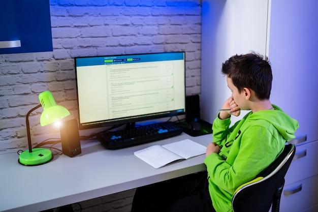 Подросток учится дома. мальчик за компьютером делает тесты. учиться в карантине. школьник во время карантина