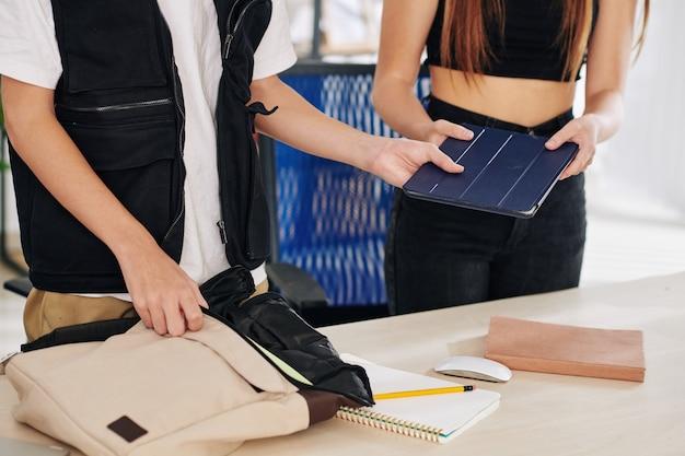 Мальчик-подросток берет планшетный компьютер из рук одноклассника и кладет в его школьную сумку