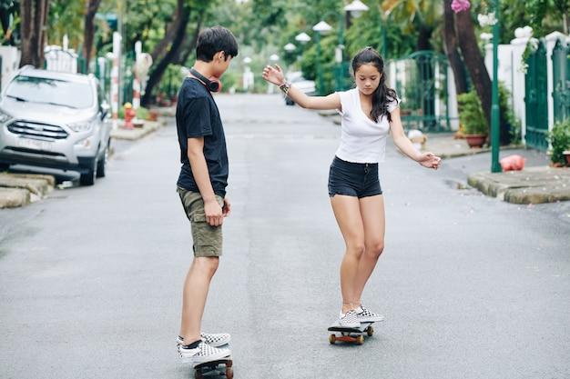 Подросток учит сестру кататься на скейтборде