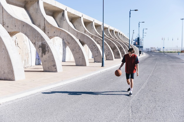 Teenage boy walking on street with basketball