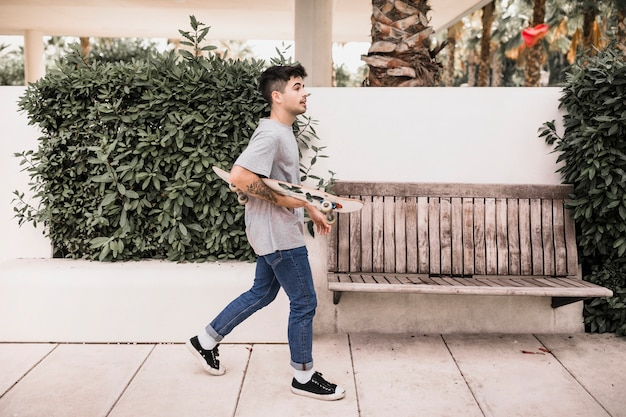 Teenage boy walking with skateboard in the park