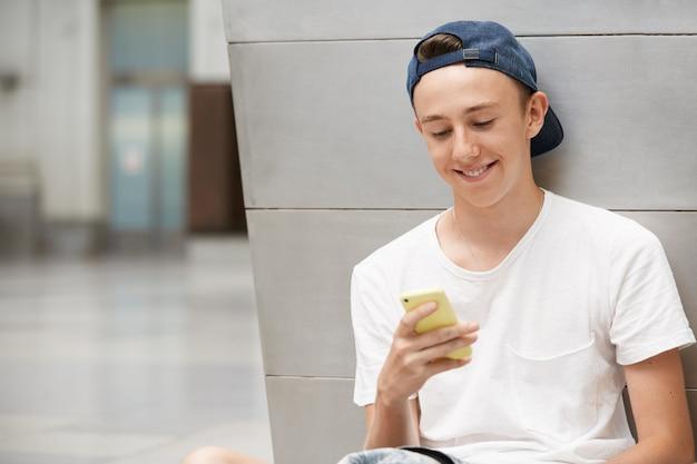 キャップを着用し、スマートフォンを使用して10代の少年