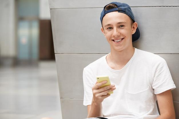 Ragazzo adolescente che indossa il cappello e utilizza lo smartphone