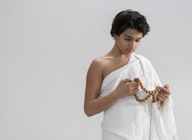 Teenage boy wearing ihram for hajj with rosary